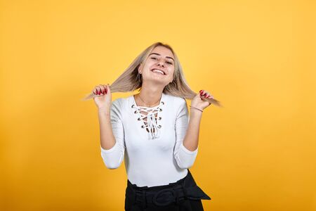Portrait of beautiful young woman in light casual clothes looking camera, holding hair isolated on orange background in studio. People sincere emotions, lifestyle concept. Stok Fotoğraf