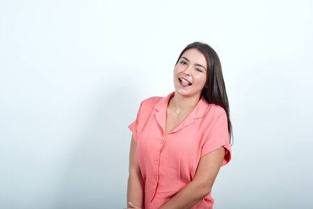 Young woman on white wall showing tongue at the camera having funny look. Joyful looking girl closed one eye Stock Photo