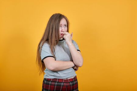 Boring young caucasian woman posing isolated on orange background in studio wearing casual shirt, keeping hand on mouth, looking hervous
