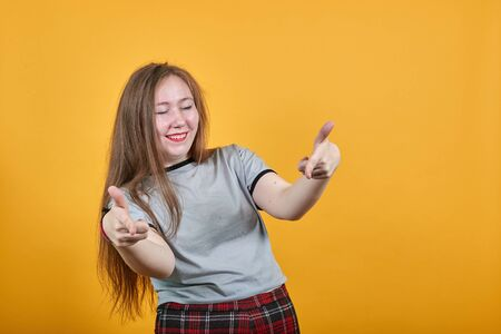 Attractive caucasian young girl over isolated orange wall wearing fashion clothes keeping fingers directly, closed eyes, smiling Zdjęcie Seryjne