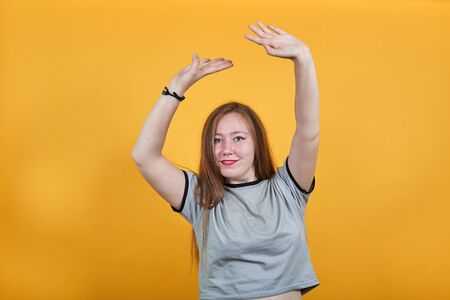 Surprised cheerful young woman in casual shirt, looking camera, spreading hands over head isolated on orange background in studio. People sincere emotions, lifestyle concept. Stok Fotoğraf
