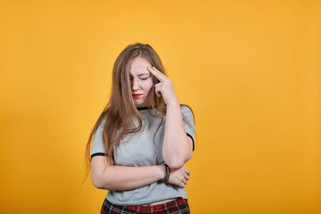 Pretty young caucasian brunette woman wearing nice gray shirt over orange background, looking funny, thinking about issue, having headache Zdjęcie Seryjne