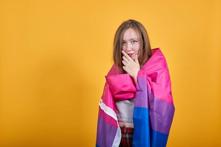 Boring young caucasian woman posing isolated on orange background in studio wearing casual shirt, keeping hand on chin, covered bisexual flag Stock Photo