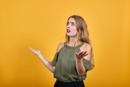 Shocked cheerful young woman in haki shirt, looking camera, spreading hands isolated on orange background in studio. People sincere emotions, lifestyle concept. Stock Photo