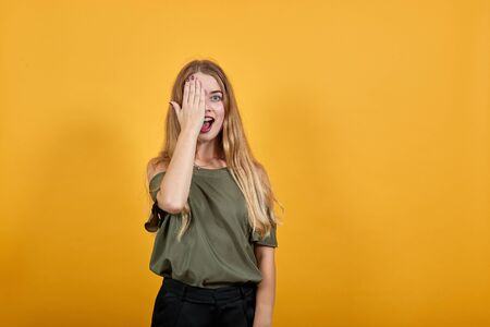 Beautiful young girl wearing shirt over isolated orange background afraid and shocked, yawing covering hands eye, keeping mouth opened