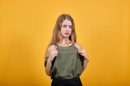 Portrait of smiling pleasant young woman in casual shirt holding shirt fingers, heart isolated on orange background in studio. People sincere emotions, lifestyle concept.