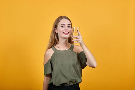 Young blonde woman girl in casual clothes posing isolated on orange wall background studio portrait, keeping glass of water Stock Photo