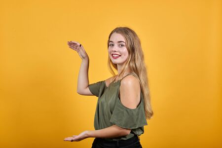 Cheerful girl in casual clothes gesturing demonstrating size with vertical workspace isolated on orange wall background. People sincere emotions, lifestyle concept.