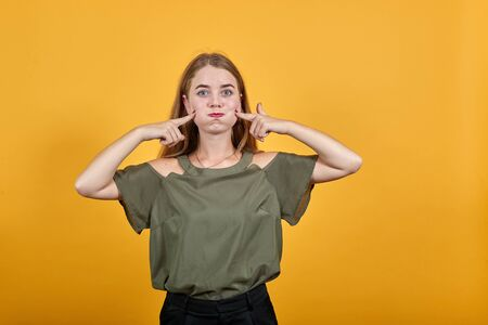 Young funny beautiful caucasian woman wearing nice shirt puffing cheeks and keeping fingers on with funny face. Mouth inflated with air, crazy expression
