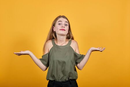 Caucasian attractive girl over orange wall making unimportant gesture while lifting the shoulders wearing haki shirt Stok Fotoğraf