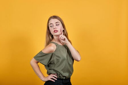 Portrait of shocked young woman in casual clothes keeping mouth wide open, keeping finger on cheek isolated on orange wall background in studio. People sincere emotions lifestyle concept.