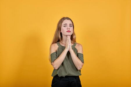 Portrait of worried young woman in vivid casual clothes looking directly, holding hands crossed, praying isolated on bright orange wall background in studio. People lifestyle concept.
