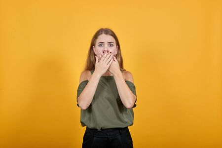 Young attractive blonde woman wearing clothes, over isolated wall with surprise facial expression, covering mouth with hands over isolated orange background