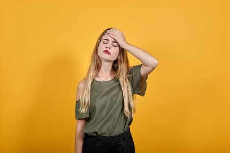 Relaxed young woman in casual clothes keeping eyes closed, with hand behind head isolated on orange wall background in studio. People sincere emotions, lifestyle concept.