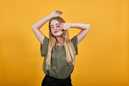 Pretty young girl over isolated orange wall wearing fashion pastel clothes true beauty, position, keeping hands up closed eyes