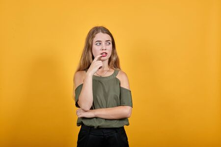 Young pretty attractive woman looking aside, opened eyes with the hand on mouth on isolated orange background wearing fashion clothes