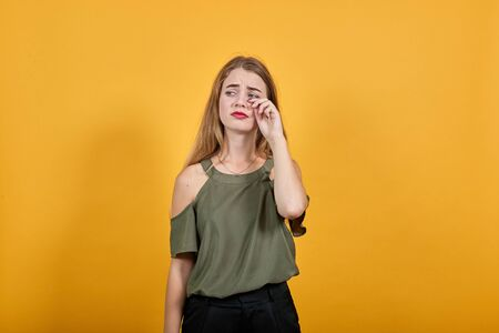 Boring young caucasian woman posing isolated on orange background in studio wearing casual shirt, keeping hand on cheek, wipes away tears