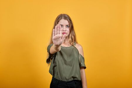 Portrait of serious young woman in casual clothes showing stop gesture with palm isolated on orange wall background in studio. People sincere emotions lifestyle concept. Stock Photo