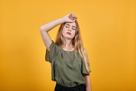 Pretty young caucasian blonde woman wearing nice pastel shirt over white background, looking funny, thinking about issue, looking tired