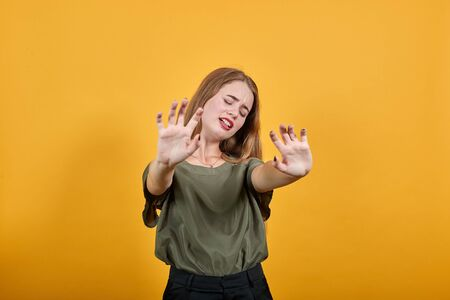Portrait of scared shocked young woman in casual clothes, rising hands showing palms, stop gesture isolated on orange wall background in studio. People sincere emotions lifestyle concept.