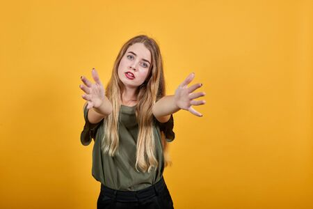 Attractive caucasian young woman wearing pastel shirt over isolated on orange wall background, spreading hands, and looking so funny, serious Foto de archivo - 134299433