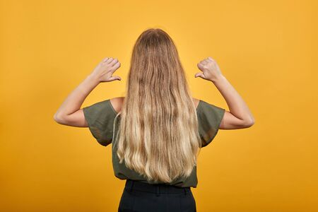 Back rear view of brunette young woman in pointing thumbs on herself isolated on orange wall background in studio. People sincere emotions, lifestyle concept.
