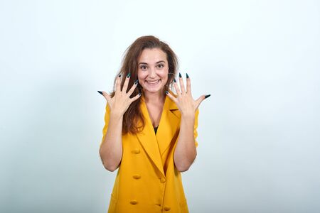 Cheerful caucasian young woman in yellow jacket showing manicure, looking happy isolated on gray background in studio. People sincere emotions, lifestyle concept. Imagens