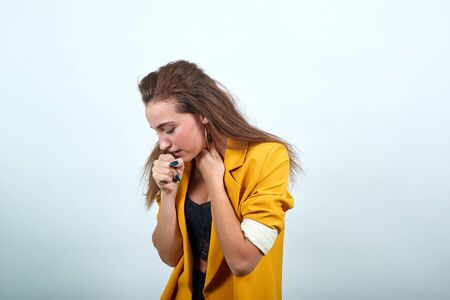 Attractive young woman in yellow jacket keeping hand on mouth, cough, looking sickness isolated on gray background in studio. People sincere emotions, lifestyle concept.