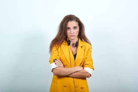 Angry caucasian woman looking directly, having headphones, holding hands crossed isolated on gray background in studio in yellow jacket. People sincere emotions, lifestyle concept. Imagens