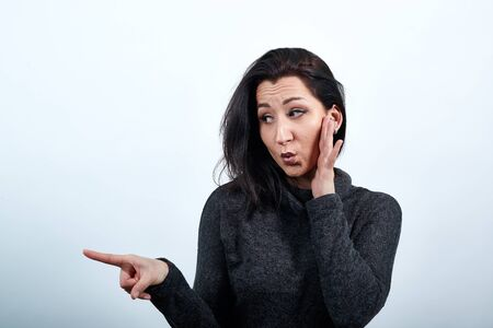 Beautiful caucasian young woman in fashion black sweater over isolated white background, holding hand on cheek, pointing aside, looking shocked. Lifestyle concept