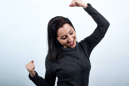 Beautiful caucasian young woman in fashion black sweater dancing, keeping fists up, looking happy over isolated white background, Lifestyle concept