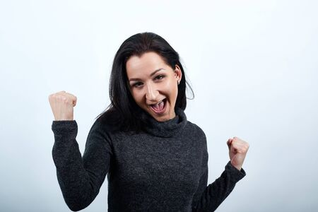 Beautiful caucasian young woman in fashion black sweater dancing, keeping fists up, looking happy over isolated white background, Lifestyle concept Stock Photo