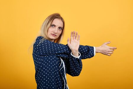 Serious caucasian young lady staying sideways, stretches hands doing stop gesture over isolated orange background in blue shirt with white polka dot. Lifestyle concept