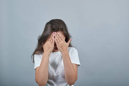 Girl in white t-shirt hides face with hands. Behind her there is gray background. Teen looks upset and unsatisfied