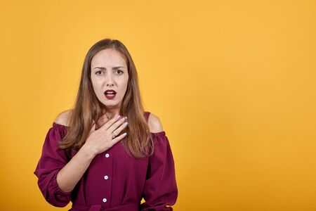 Young woman in burgundy bluse with shocked facial expression. Behind her is isolated orange wall.