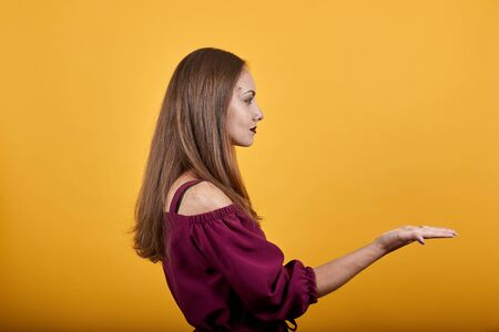 Young woman in burgundy bluse over orange isolated background extending hand to right side for inviting to come