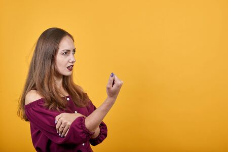 Young girl shows her fist. She looks menacing, displeased. Behind her there is wall of orange color. Angry gesture displays ladys displeasure Stock Photo