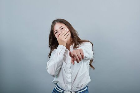 Happy young woman in fashion white shirt isolated on gray background in studio covering mouth with hand, pointing finger at camera People sincere emotions, lifestyle concept.