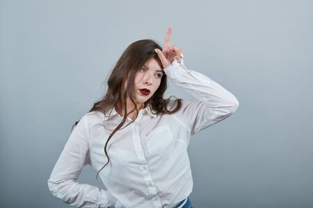 Caucasian attractive young brunette woman over isolated gray background wearing casual white shirt, holding hand on forehead, doing loser gesture. People lifestyle concepte.