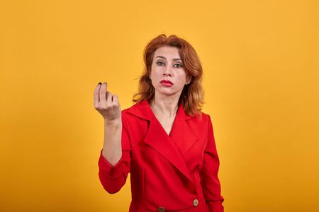 Disappointed caucasian young woman keeping fingers together, looking at camera wearing fashion red jacket over isolated orange background. People lifestyle concept. Imagens