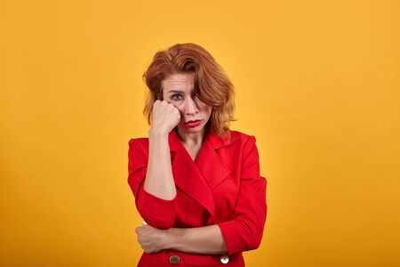 Boreing caucasian woman looking at camera, pointing fist aon cheek, keeping hand on stomach wearing fashion red jacket over isolated orange background. People lifestyle concept.