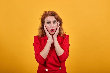 Unhappy shocked caucasian young woman keeping hand on cheeks with opened mouth, confused, wearing fashion red jacket over isolated orange background. People lifestyle concept. Imagens