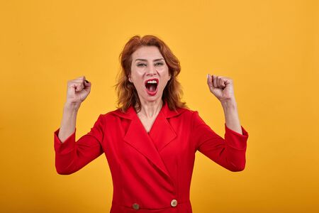 Caucasian young woman wearing fashion red jacket over isolated orange background keeping fists up, screaming. People lifestyle concept.