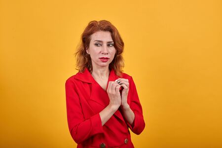 Unhappy attractive young woman keeping hands together, pondering a plan wearing fashion red jacket over isolated orange background. People lifestyle concept.