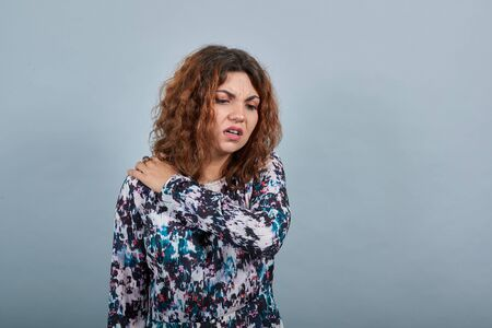 Unhappy charming young lady over isolated gray background in fashion shirt keeping hand on neck, pain in muscules. People emotions. Lifestyle concept