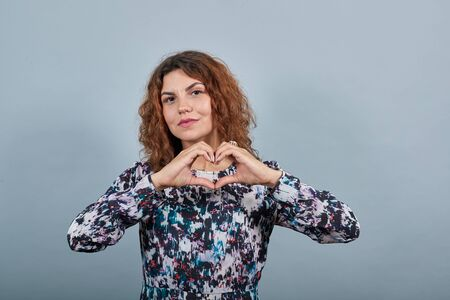 Cheerful attractive young woman over isolated gray background in fashion shirt doing shape of heart, looking at camera. People emotions. Lifestyle concept