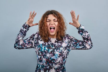 Crazy young caucasian young woman showing tongue, keeping hands near face over isolated gray background in fashion shirt. Lifestyle concept Imagens