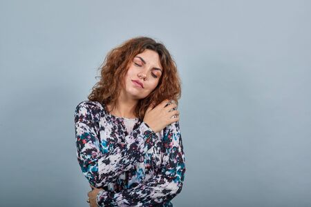 Charming caucasian young woman hugging herself with closed eyes, looking calm over isolated gray background in fashion shirt. Lifestyle concept