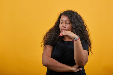 Serious afro-american young woman with overweight over isolated orange background wearing fashion black shirt closed eyes, keeping hand near face . People lifestyle concept.