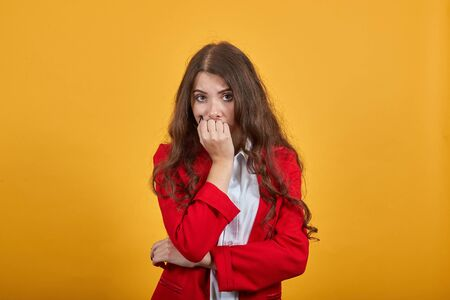 Scared young woman in fashion white shirt and red jacket biting fingers, holding hand on stomach, looking at camera isolated on orange background in studio. People sincere emotions, lifestyle concept.